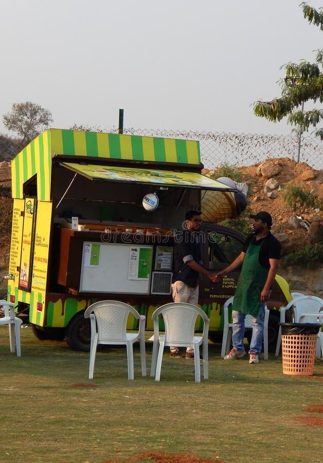 Les personnes indiennes achètent la nourriture de rue aux camions de nourriture postés dans le terrain découvert image libre de droits