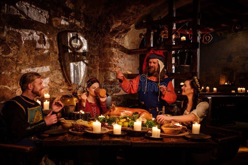 Les personnes médiévales mangent et boivent dans l'intérieur antique de cuisine de château photos libres de droits