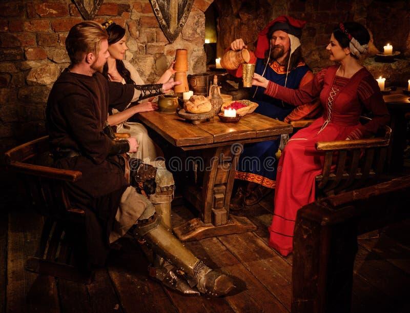 Les personnes médiévales mangent et boivent dans la taverne antique de château image stock