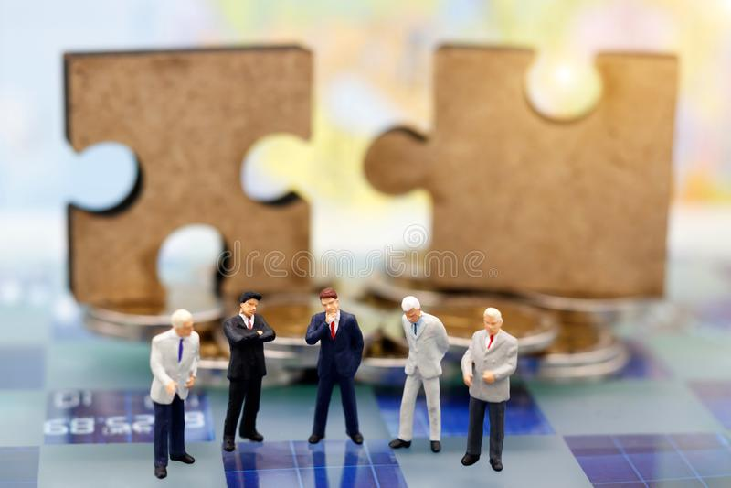 Les personnes miniatures, homme d'affaires pensent avec le puzzle denteux image stock