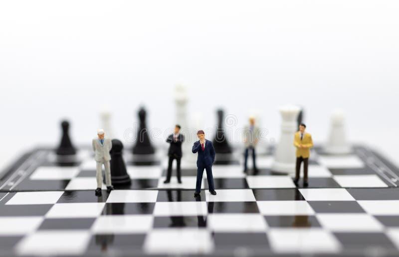 Les personnes miniatures, hommes d'affaires de groupe se tenant sur le jeu d'échecs, solution de pensée pour la simulation de ges photographie stock libre de droits