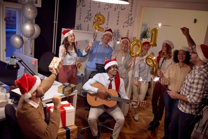 Les personnes multi-ethniques heureuses de groupe d'affaires ont l'amusement et la danse dans le chapeau de Santa à la partie de  photos libres de droits