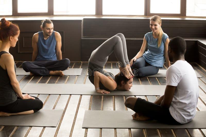 Les personnes multiraciales regardant l'instructeur exécutant le yoga posent à photos stock