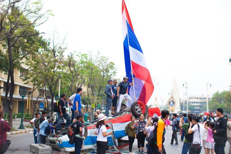 Les personnes non identifiées se tiennent sur la voiture de police avec le drapeau thaïlandais photo stock