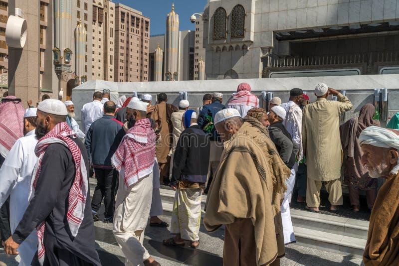 Les personnes non identifiées sont l'eau de zamzam buvant chez le Nabawi Mosq image stock