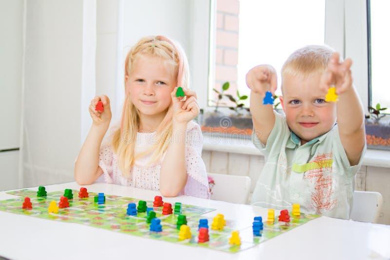 les personnes rouges de petite prise blonde de fille figurent à disposition déchets de bois jaunes, bleus, verts chez le jeu des  photo stock