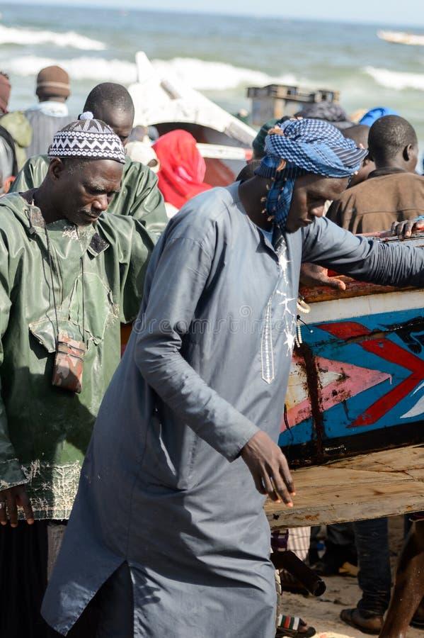 Les personnes sénégalaises non identifiées tirent le bateau à l'eau sur le Th images libres de droits