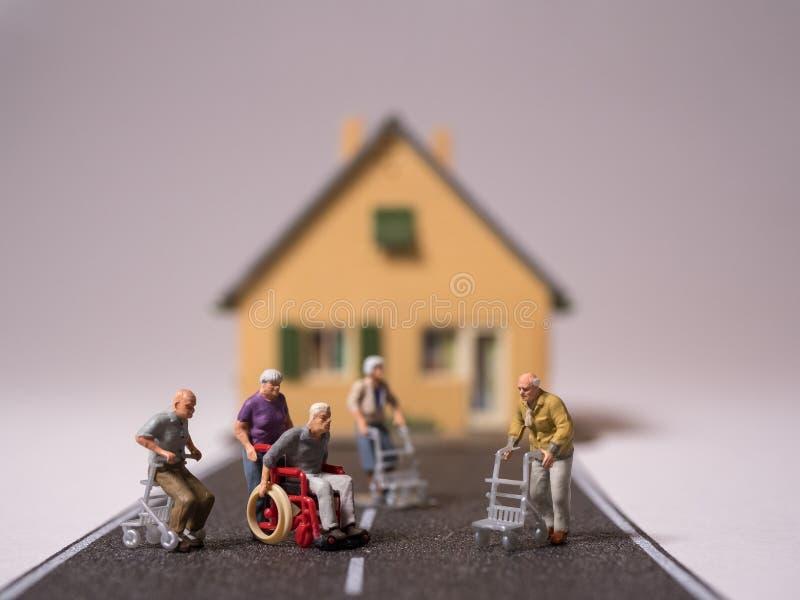 Les personnes supérieures de Minitature avec le fauteuil roulant et les marcheurs ont laissé seul sur la rue photos stock