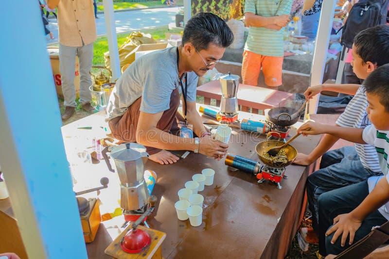 Les personnes Unacquainted de la Thaïlande enseignent à des enfants comment faire à la Thaïlande le café rôti du sud Festival de  photo libre de droits