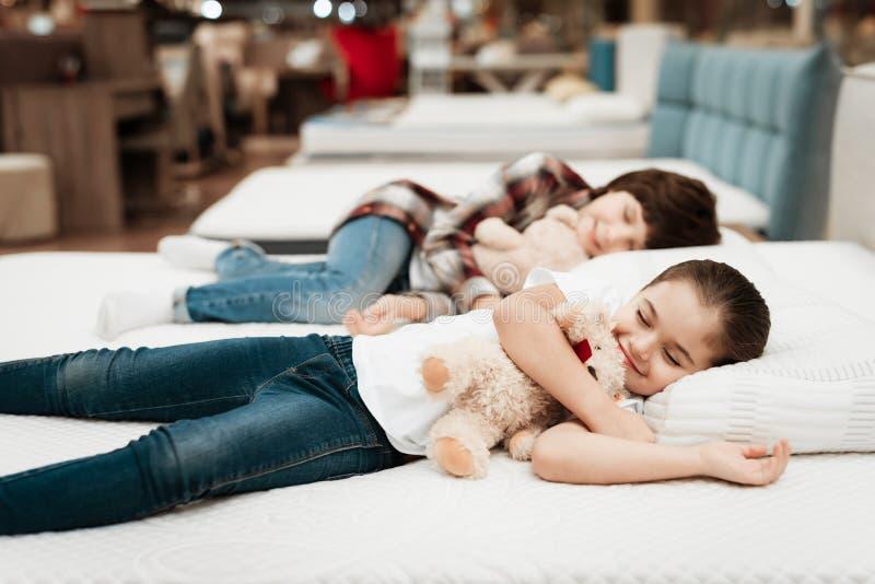 Les petites étreintes heureuses de fille soutiennent se trouver sur le lit Dans des sommeils de petit garçon de fond images stock