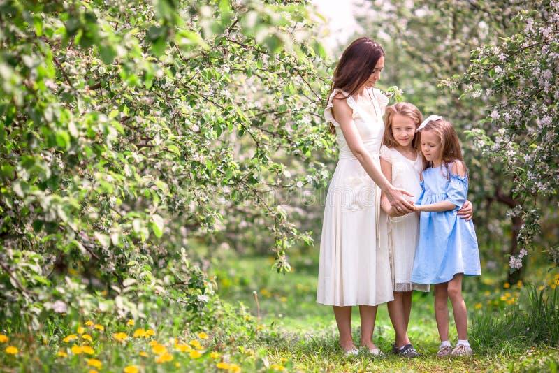 Les petites filles adorables avec la jeune mère dans la cerise de floraison font du jardinage la belle journée de printemps photographie stock