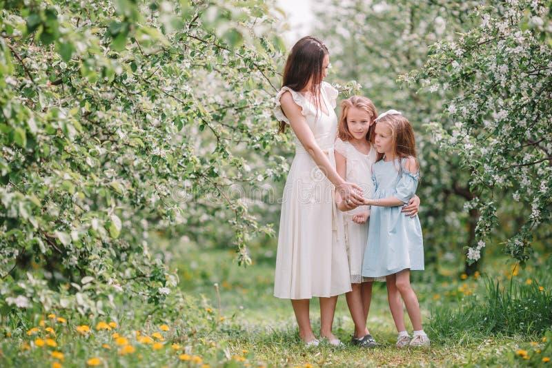 Les petites filles adorables avec la jeune m?re dans la cerise de floraison font du jardinage la belle journ?e de printemps photo stock