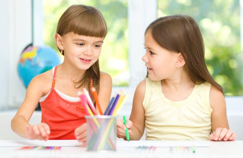 Les petites filles dessinent à l'aide des crayons images stock