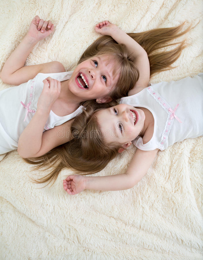 Les petites filles heureuses se trouvant dessus soutiennent d'en haut photos libres de droits