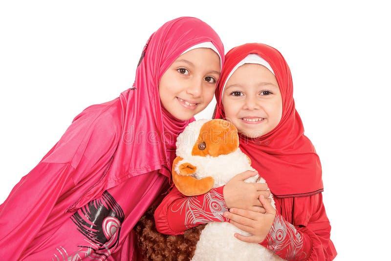 Les petites filles musulmanes heureuses jouant avec des moutons jouent - célébrer E images libres de droits