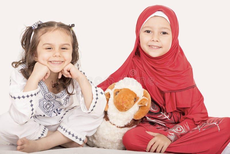 Les petites filles musulmanes heureuses jouant avec des moutons jouent - célébrer E photo stock