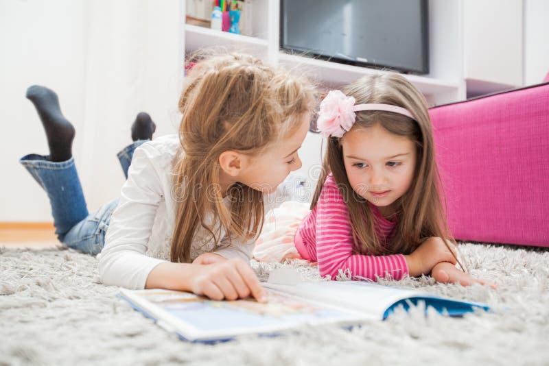 Les petites filles ont lu le livre photos stock