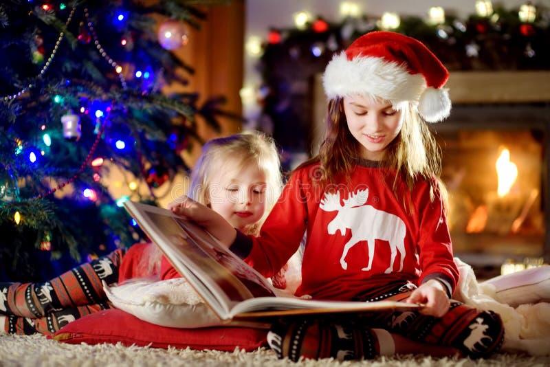 Les petites soeurs heureuses lisant une histoire réservent ensemble par une cheminée dans un salon foncé confortable le réveillon image stock