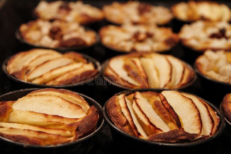 Les petites tartes aux pommes faites maison ont fraîchement fait chacun cuire au four dans son moule photographie stock