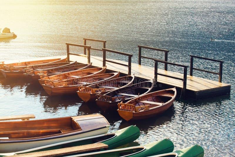 Les petits bateaux et canoës en bois ont attaché pour vider le pilier image libre de droits