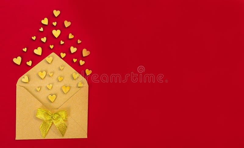 Les petits coeurs en bois volent hors de l'enveloppe sur un fond rouge Jour du `s de Valentine Concept d'amour Cadeau, message po image libre de droits