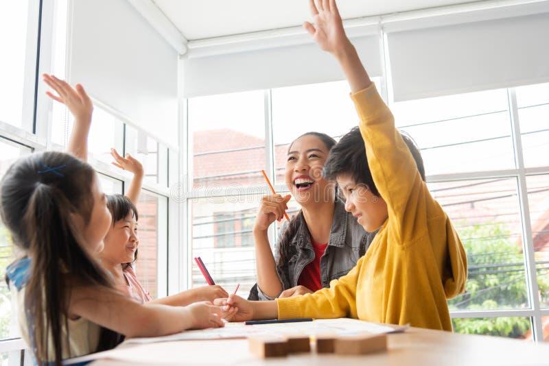 Les petits enfants asiatiques heureux soulèvent leurs mains tandis que thé femelle image stock