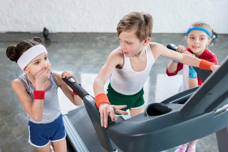 Les petits enfants dans les vêtements de sport s'exerçant sur le tapis roulant dans le gymnase, enfants folâtrent le concept d'éc images libres de droits