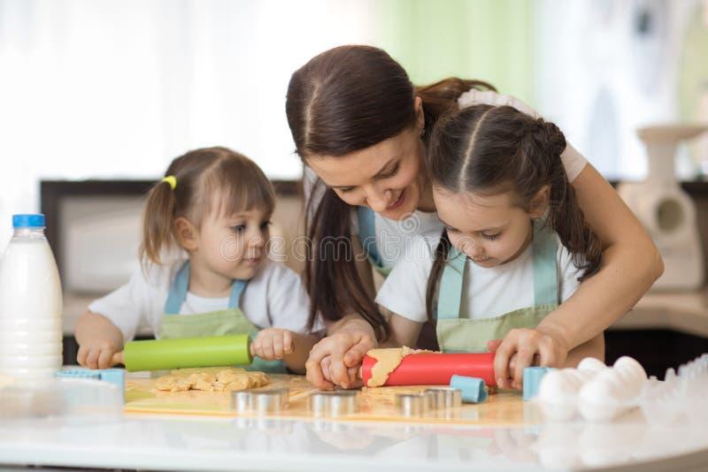 Les petits enfants mignons et leur belle maman dans les tabliers sont jouants et riants tout en malaxant la pâte dans la cuisine photographie stock