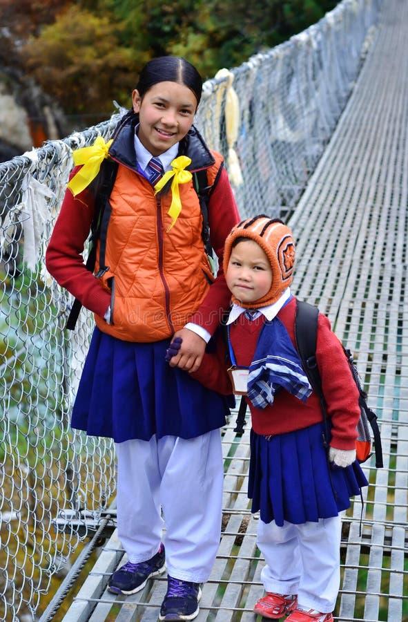 Les petits enfants non identifiés rentrent à la maison de l'école dans Phakding, Népal photo libre de droits