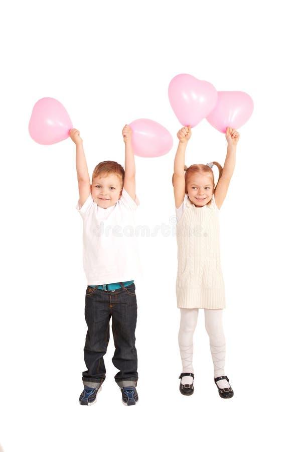 Les petits enfants tenant et prenant le coeur monte en ballon image libre de droits