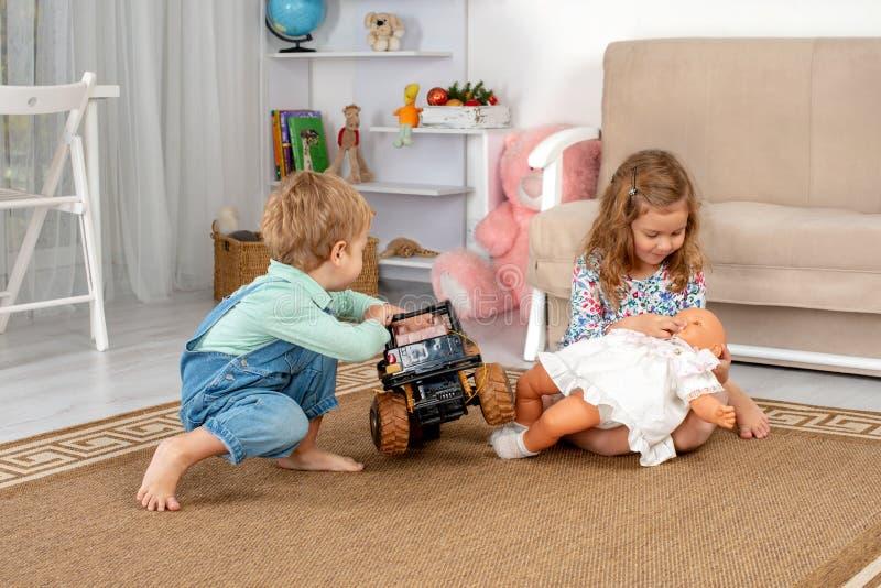 Les petits enfants, un garçon et une fille, s'asseyent sur le plancher sur une couverture dedans images stock