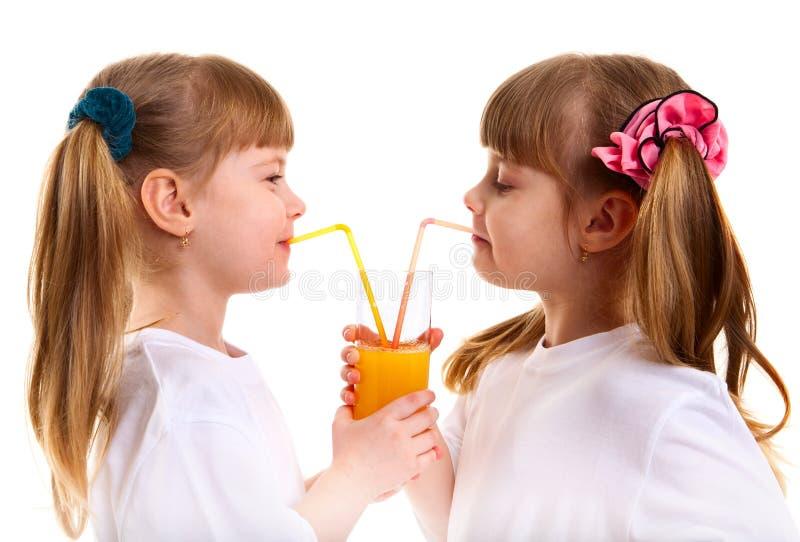 Les petits fille-jumeaux boivent du jus d'orange photos libres de droits