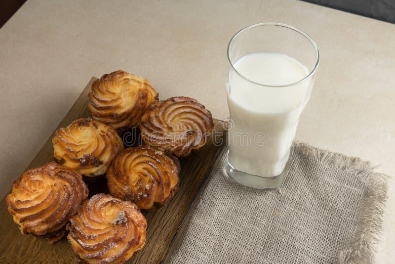 Les petits gâteaux de gâteau au fromage de chocolat et un verre de lait pour le petit déjeuner copient le spase photos libres de droits