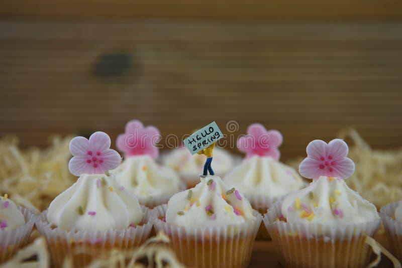Les petits gâteaux de vanille ont complété avec des fleurs roses glacées et un panneau miniature de signe pour bonjour le ressort photographie stock libre de droits