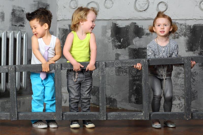 Les petits garçons et la fille portent ensemble les escaliers en bois image libre de droits
