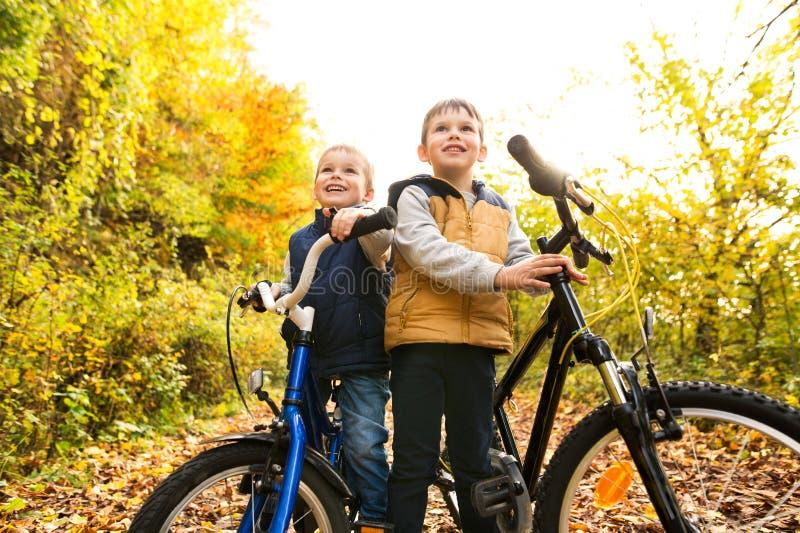 Les petits garçons mignons faisant un cycle en automne ensoleillé se garent photo stock