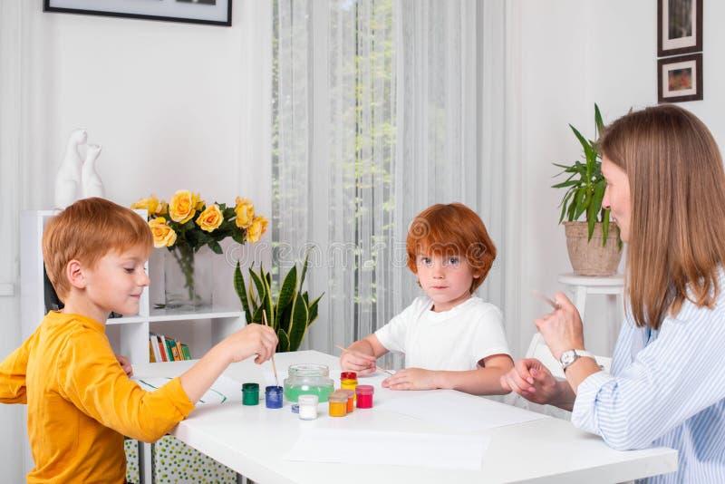 Les petits garçons roux avec une bonne d'enfants ou une mère ou un professeur s'asseyent à la table et à la peinture avec des cou images libres de droits