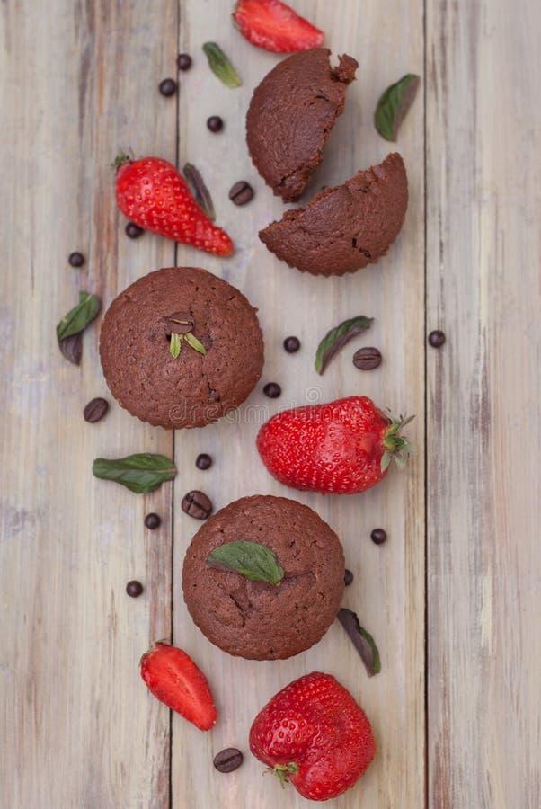 Les petits pains de chocolat avec les feuilles en bon état de fraise au-dessus de Gray Background Breakfast rustique abandonnent photo stock