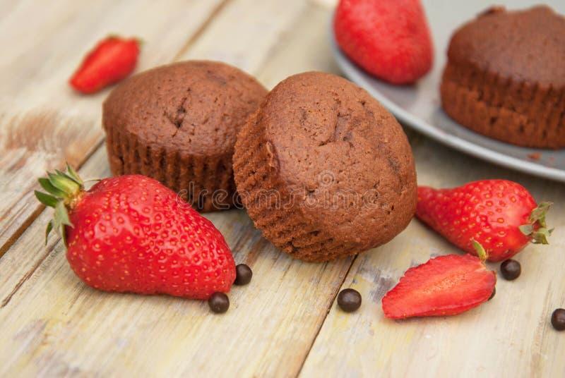 Les petits pains de chocolat avec les feuilles en bon état de fraise au-dessus de Gray Background Breakfast rustique abandonnent photographie stock libre de droits