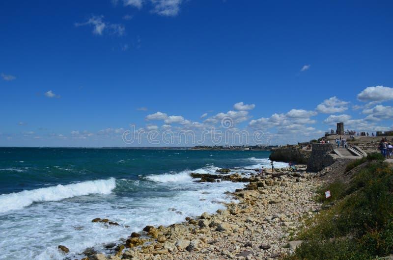 Les petits pains de la Mer Noire dans les vagues avec la mousse sur un rivage rocheux image libre de droits