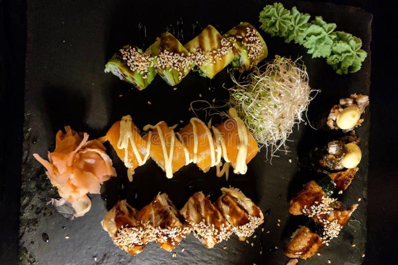 Les petits pains de sushi réglés ont servi sur l'ardoise en pierre noire sur le fond foncé photos libres de droits