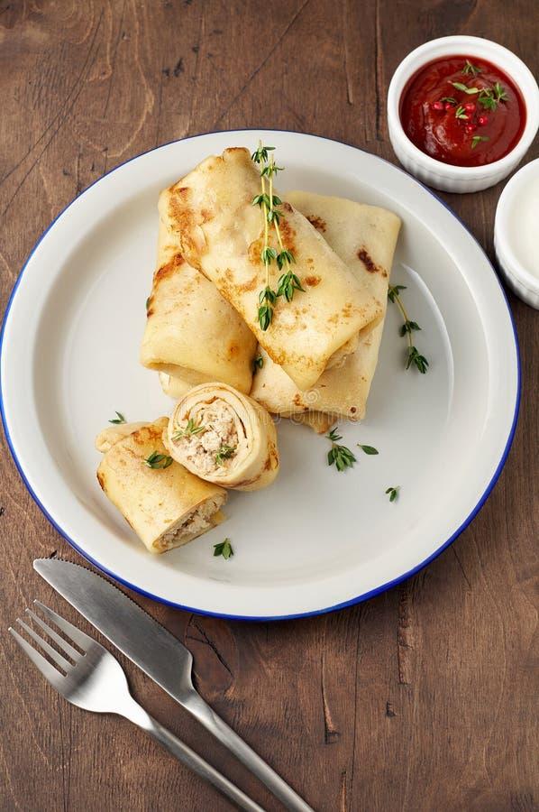 Les petits pains savoureux de crêpe avec le remplissage de viande hachée ont servi avec la sauce de crème sure et tomate photo stock