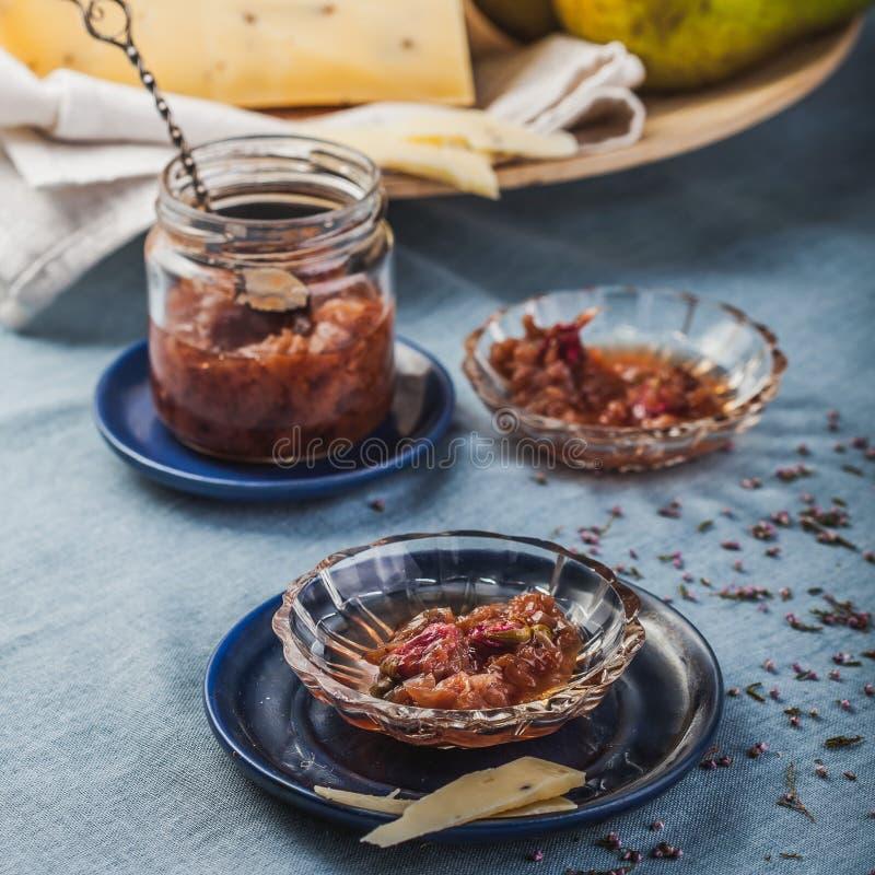 Les petits plats de confiture avec le pétale de rose bloquent, des poires et un grand morceau de fromage sur une nappe de turquoi photos libres de droits