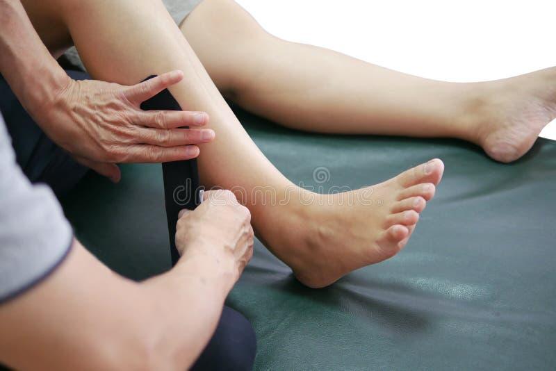 Les physiothérapeutes emploient la méthode de cinésiologie attachant du ruban adhésif dans les muscles de la jambe du patient pou image stock