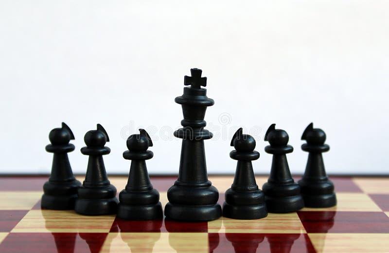 Les pièces d'échecs noires se tiennent devant le roi et derrière lui gages images stock