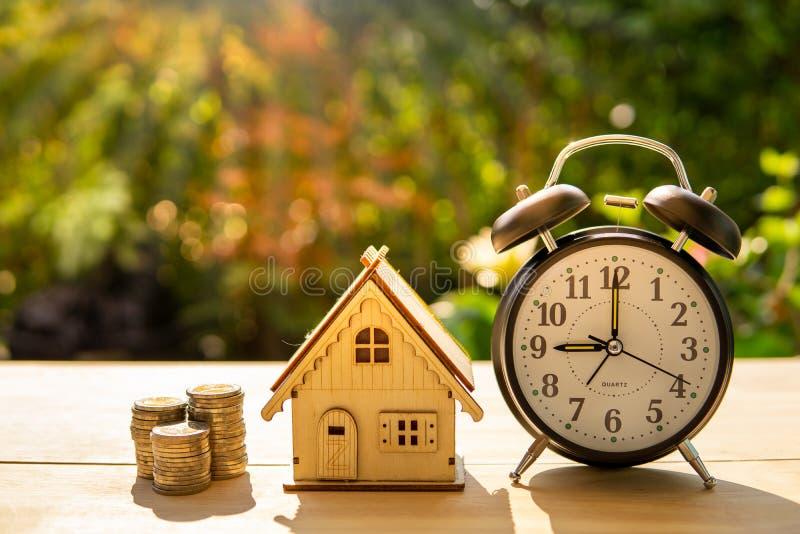 Les pièces de monnaie d'argent de maison et la pile de réveil sur le fond en bois de table et de coucher du soleil dans le paquet photographie stock libre de droits