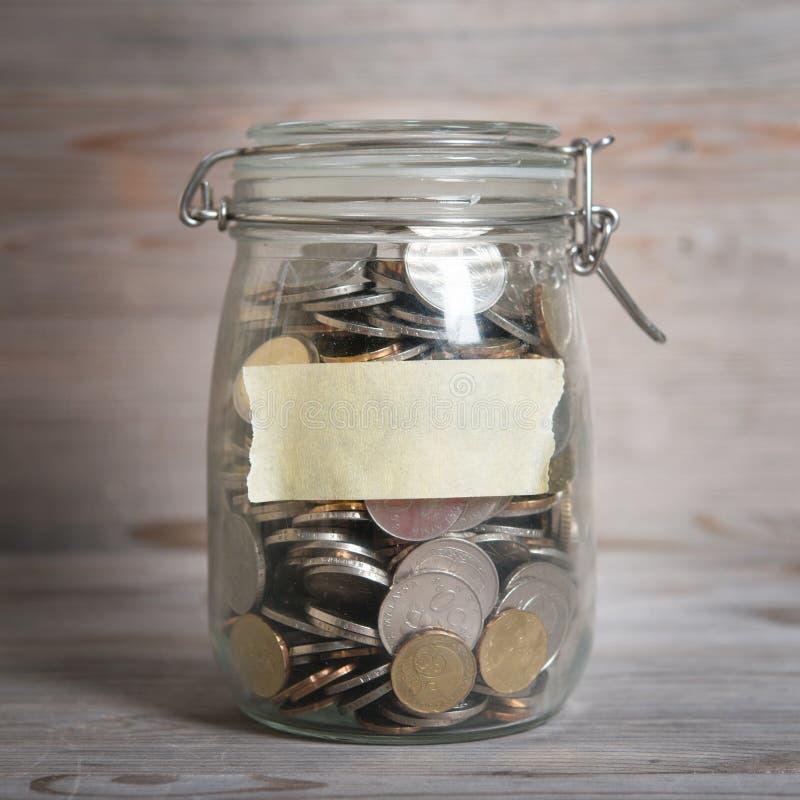 Les pièces de monnaie en argent en verre cognent avec le label vide photo stock