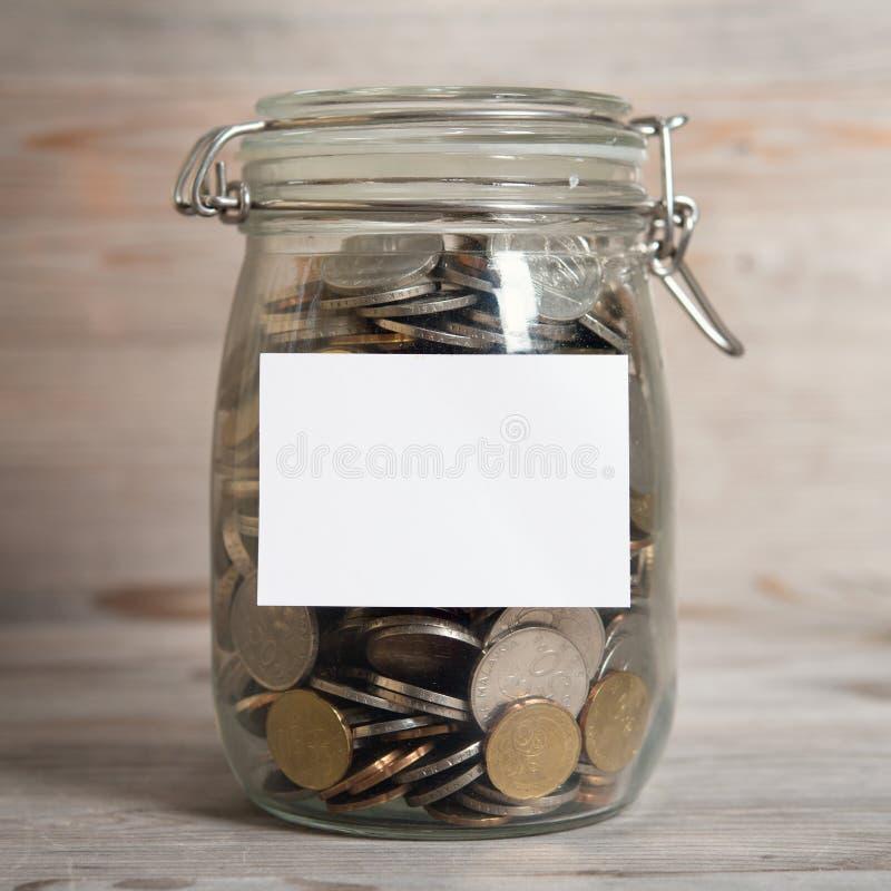 Les pièces de monnaie en argent en verre cognent avec le label vide blanc photographie stock