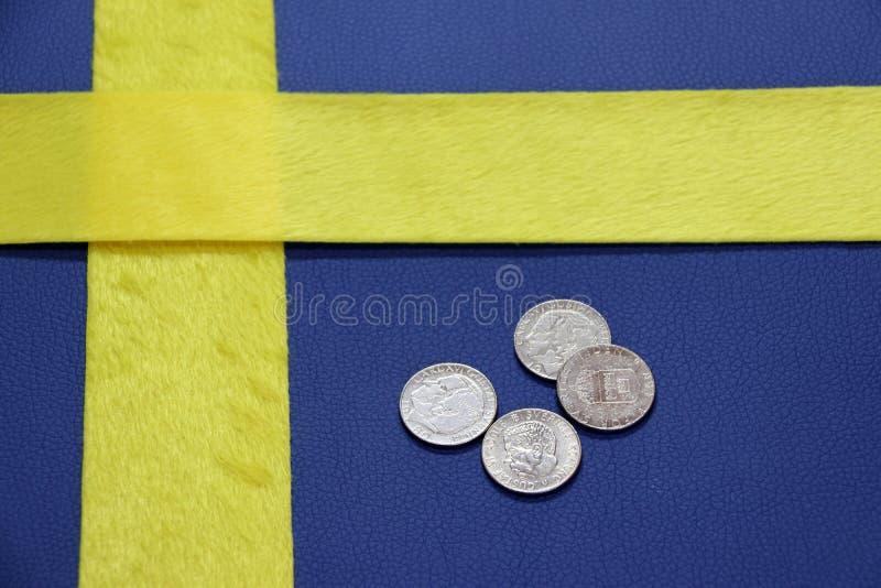 Les pièces de monnaie de la Suède sur le cuir bleu de PVC avec le tissu jaune, ont mis comme un drapeau de nation de la Suède photos stock