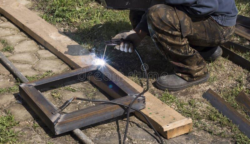 Les pièces professionnelles en métal de soudages de soudeuse par le soudage électrique, étincelle en raison de la haute températu photos libres de droits